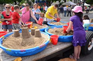 Children were able to take part in a sand castle competition in downtown Warsaw by utilize kiddie pools filled with moist sand.  (photo by Alyssa Richardson)