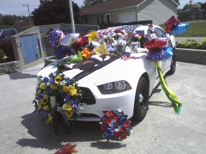 Akron Town Marshal Tim Fleck's patrol vehicle is covered with flowers and other tokens of remembrance left in his honor. (Photo provided by John Adams)