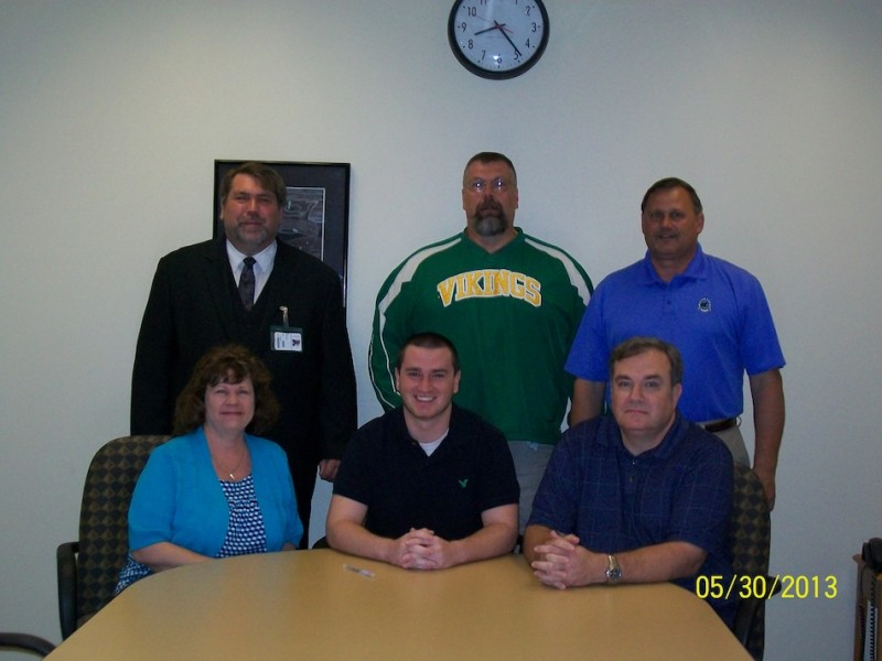 Jacob Ritchey of Tippecanoe Valley will continue his football career at Manchester University. Ritchey is pictured above in front, flanked by his parents Angie and Steve. In back are TVHS principal Kirk Doehrmann, football coach Jeff Shriver and athletic director Duane Burkhart (Photo provided)