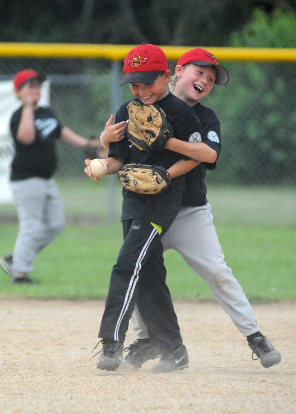 Brylee Vandiver gets a hug from teammate Braden Mickley after making a great catch for the Red Wings.