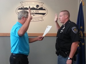 Warsaw Mayor Joe Thallemer swears in Warsaw Police Officer Ross Minear, who recently successfully completed his probationary term with the department. (Photo by Stacey Page)