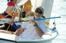 Brad Wagnon smiles while sailing campers on his Lightning.