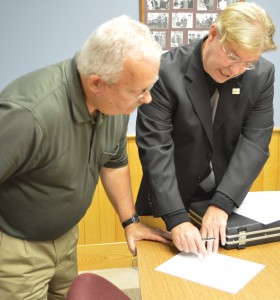 Steve Unruh prepares to sign necessary documents being shown him by Randy Girod, Kosciusko County Republican Chairman. (Photo by Deb Patterson)