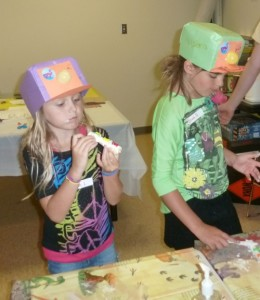 Hannah Likens and Olivia Ousley enjoy bone-shaped cookies during Friday Family Food and Fun where they explored digging underground with crafts and treats. (Photo provided)