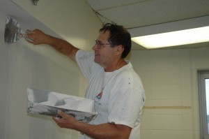 Jim Brita of the Strahm Group Inc., Fort Wayne, does drywall work in one of the C wing rooms at Wawasee High School. Eventually the walls will be painted in this room and others in the C wing as part of summer construction or renovation projects within the Wawasee Community School Corp. (Photo by Tim Ashley)