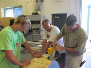 Student Drew Denney, left, watches as Ed Waltz, right, building trades instructor for Wawasee High School, uses a saw. In the middle is Jamie McAdams, WHS industrial arts teacher. As part of the Early Career Options Summer Challenge, at-risk students helped build a shed for Habitat for Humanity. (Photo provided