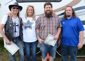 Stacey Page is pictured with the winners of the Kosciusko's Got Talent contest hosted by StaceyPageOnline.com. From left are Kevin Kyle of the Guy Franklin Band, which placed as runner up; Josh Jacoby, representing Plaxton & The Void, the grand prize winner; and Brandon Bussard is also of the Guy Franklin Band. (Photo by Alyssa Richardson)