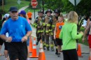 Syracuse firefighters Quinn Hunter, Matt Dunithan and Brian Simmons cross the finish line in full gear after completing the 3.3-mile course.