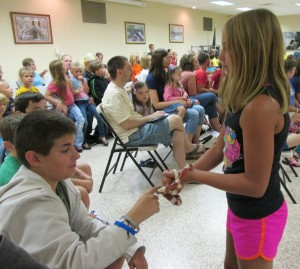 """Jessica Murphy introduces a corn snake named """"Candy Cane"""" to Matt Rhodes at the Library's """"Critters That Dig"""" Live Animal Show presented by Mark's Ark. (Photo provided)"""