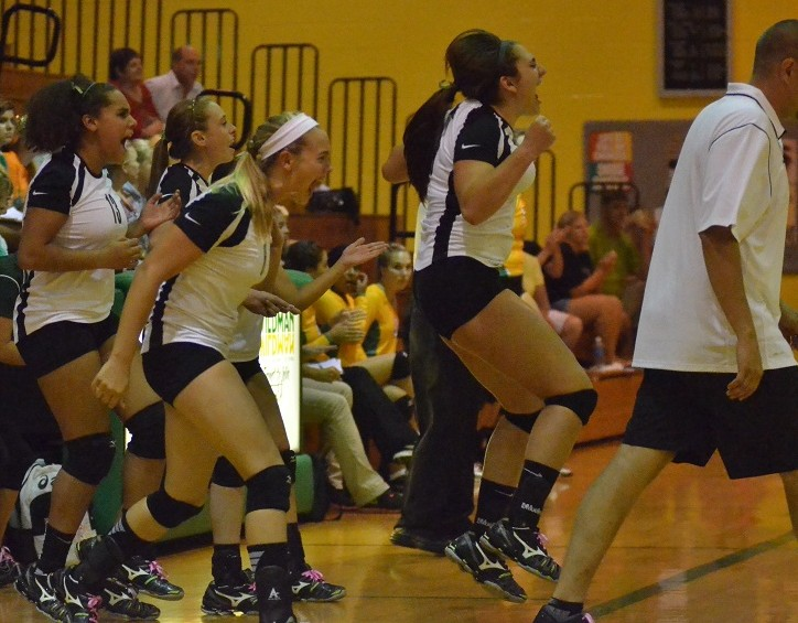 The Lady Warrior bench reacts to the winning point Tuesday night in Akron.