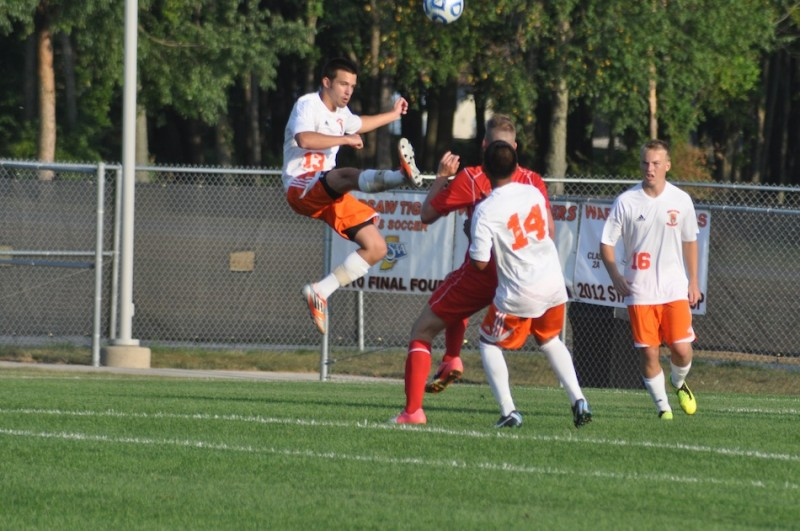 Warsaw senior Matt Williams (No. 13) makes a play on the ball during a 3-0 win over Plymouth Thursday. Also pictured for the No. 2 Tigers are Miguel Rivera (No. 14) and Caleb Klusman (No. 16). (Photos by Amanda Farrell)