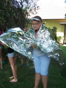 Austi Swanson learns how to keep herself warm using an aluminum blanket during the Unofficial Hunger Games Program sponsored by the Milford Public Library. (Photo provided)