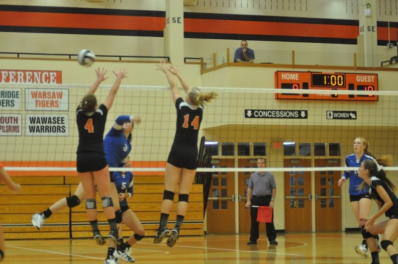 Warsaw's Emily Poe and Katie Voelz attempt to block a Marian hitter Monday night (Photo by Amanda Farrell)