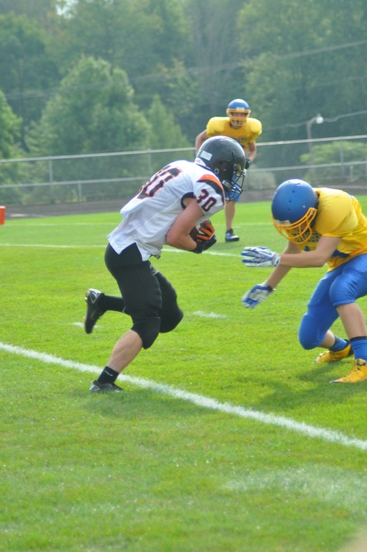 Justin Arscott gains some yardage for the undefeated Warsaw JV team Saturday.