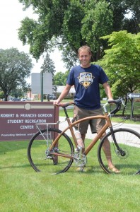 Jay Kinsinger, who owns a cottage on Dewart Lake, shows off the hand crafted wooden bicycle he built and is riding on the tour (Photo by Scott Davidson)