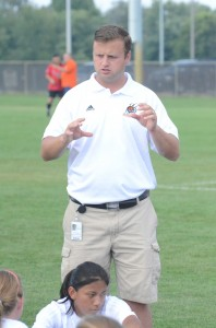 Warsaw girls soccer coach Peter Lucht makes a point with his team at halftime Monday night at WCHS.