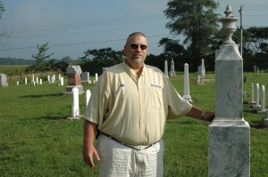Rob Edling, Seward Township trustee, stands by one of the tombstones restored in Franklin Cemetery during a major restoration project. (Photo by Tim Ashley)