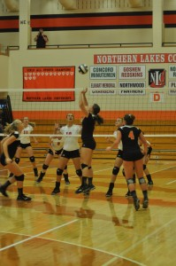 Megan Chauncey sets the ball for Warsaw Thursday night as Katie Voelz (left) and Emily Poe (right) look on.