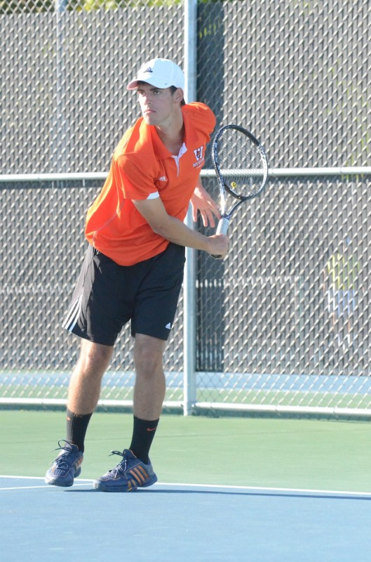 Senior Kyle Wettschurack watches his serve in No. 1 doubles play for Warsaw versus Penn Monday at WCHS.