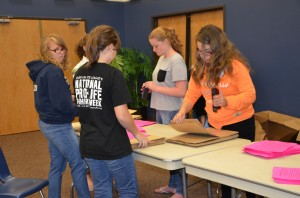 Students work to prepare the last of 4,000 paper bags that will be distributed to homes throughout the area for non-perishable food donations.