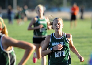 Wawasee freshman Molly Swartz strains to finish the race as teammate Courtney Linnemeier chugs in steps behind.