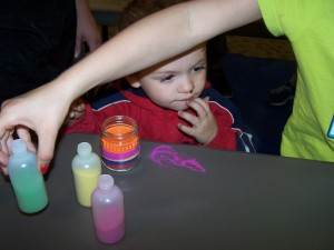David Owens, with his sister's help, makes sand jar art with a baby food jar and colored sand at the Milford Public Library.