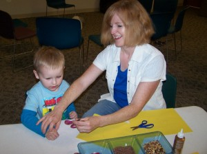 Patty Kratzer helps her grandson, Lukas Kratzer, cut  out a sunflower at story time. The theme was seeds and the children made sunflowers by gluing seeds in the middle of a yellow flower. These flowers are on display by the South door of the Milford Public Library.   (Photo provided)