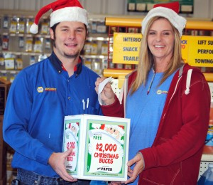 Tim Bowling, left, and Dawn Pelikant, NAPA Auto Parts, Syracuse, show how to enter the Christmas Bucks Contest. (Photo by Martha Stoelting)