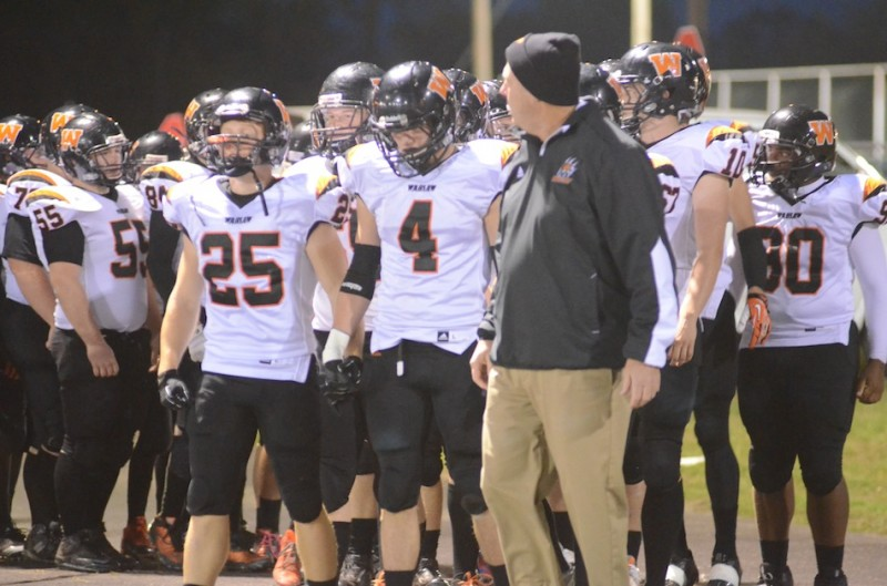 Warsaw seniors Tanner Balazs (No. 25) and Gabe Furnivall (No. 4) prepare to lead their team on to the field at Concord Friday night.