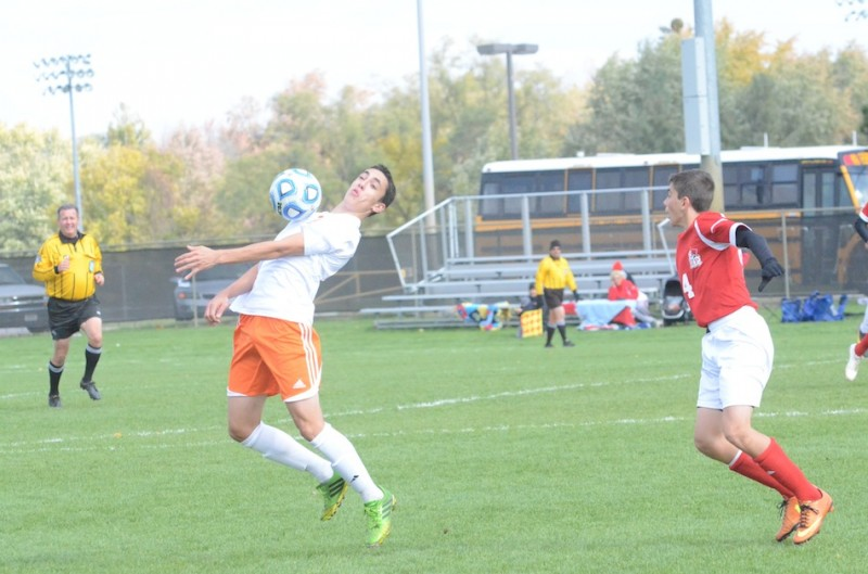 Zach Tucker of Warsaw plays the ball as Michael Tanchevski of Crown Point looks on Saturday. The No. 4 Bulldogs beat the No. 9 Tigers 1-0 in a semifinal match of the Class 2-A Warsaw Semistate (Photos by Scott Davidson)