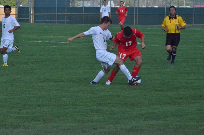 Michael Pena tries to clear a ball through the legs of Plymouth's Cesar Aguilar. Aguilar had two goals for the Pilgrims.