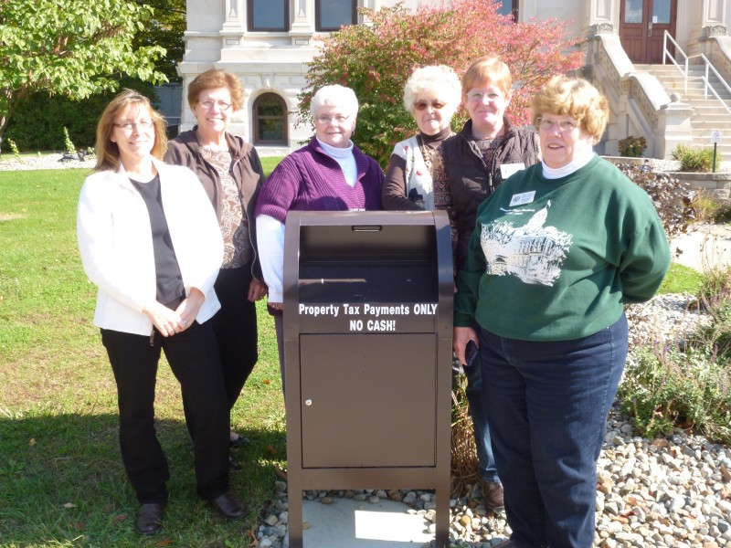 Kosciusko County Treasurer's Office employees Brenda Smits, Janet Helton, Lila Christner, Delsey Walls; Rhonda Helser, chief deputy; and Sue Ann Mitchell, Kosciusko County Treasurer are anxiously awaiting payments to be dropped in the box located on the west side of the Courthouse on Lake Street.  Payments can be dropped in the box until the tax deadline Nov. 12.  (Photo provided)