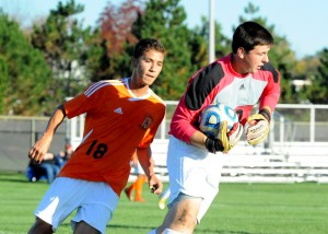 Culver Academy goalkeeper Perley Provost makes one of his six saves despite pressure from Alex Climaco.