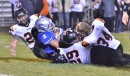 Darren Schaefer (34) loses his helmet as a group of Tigers bring down Carroll's Drue Tranquill.