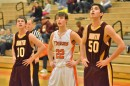 Tim Swanson of Warsaw waits for a teammate to shoot a free throw. Swanson stands between Bloomington North's Jacob Treadway (10) and C.J. Nolting (50).