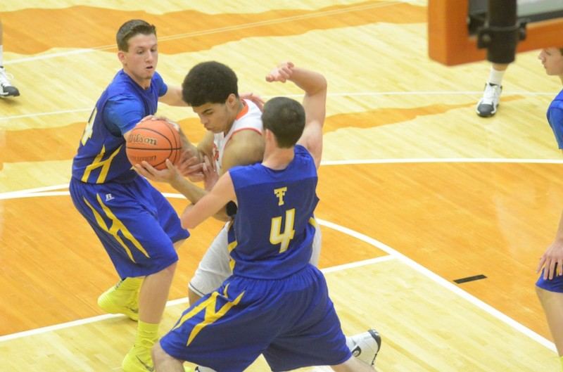 Warsaw's Rashaan Jackson is bottled up in the lane by Joey Corder (No. 4) and Tanner Shepherd of Triton.