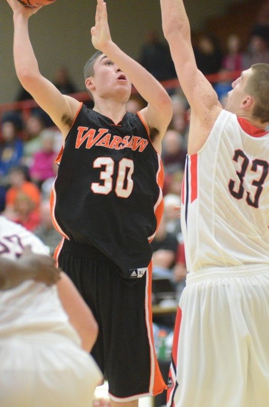 Warsaw's Jake Mangas goes up over Will Stueve of NorthWood Friday night.