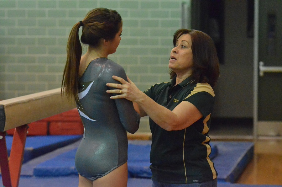 Wawasee head coach Nike Prather gives some tips to Jade Skelton following the freshman's performance on the beam.