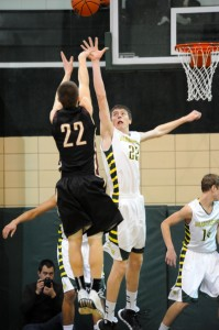 Chase Myers of Wawasee contests the jump shot of Columbia City's Justin Bachelder Saturday night. (Photos by Mike Deak)