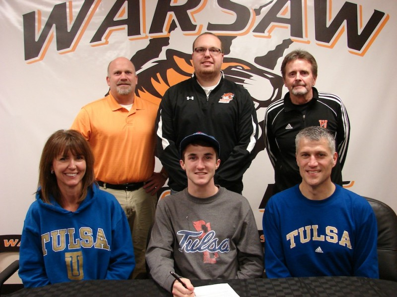 WCHS senior Ellis Coon signs Thursday to continue his track and cross country career at Tulsa University. Coon is surrounded by his parents Christine and Michael. In back are WCHS Athletic Director Dave Anson, WCHS track and cross country assistant coach Rob Peters and WCHS cross country head coach Jim Mills (Photo provided)