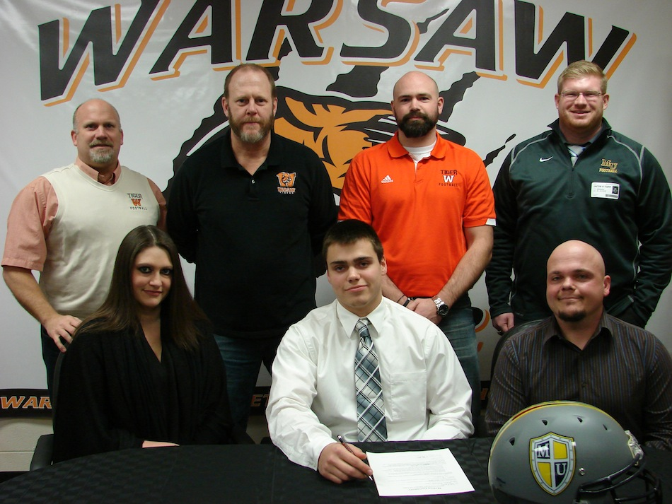 WCHS star tailback Tristan McClone signed Friday  to play football at Marian University. McClone is flanked by his parents Carrie and Dustin.  In back are WCHS Athletic Director Dave Anson, WCHS football coach Phil Jensen, WCHS defensive coordinator Kris Hueber and Marian assistant coach Jacob Topp (Photo provided)