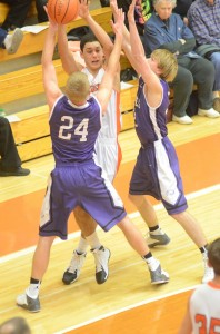 Riley Rhoades of the Tigers looks to make a pass through a pair of Elkhart Christian defenders.