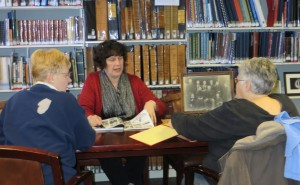 Beth Smith (center), director of the Library's Local History and Genealogy Center, explains to Faye Myer (left) and Becky Pressler (right) how to identify old photos during last week's Glean Team. This group meets at 10 a.m. the first, second, and third Wednesdays of each month to collaborate on genealogy projects. (Photo provided)