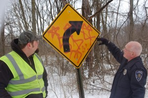 Kosciusko County Sign Technician Jeff Beeler, left, and gang specialist Officer Mike Cox, Warsaw Police Department, discuss the meaning of symbols painted on a sign on Hoss Hill Road, North Webster. The road is full of signs the county will have to replace due to gang-related tagging.