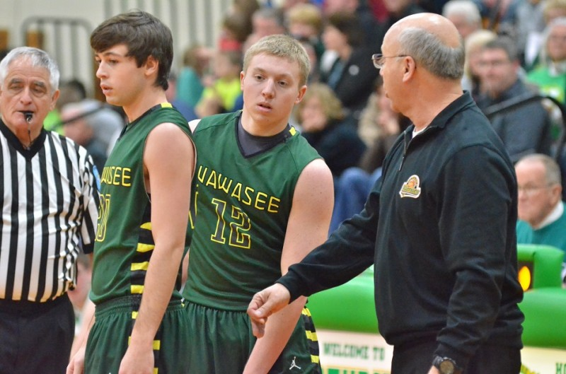 Jake Hutchinson (left) and Jeffrey Moore (center) get coached up by Steve Wiktorowski (right) before heading back on to the court.