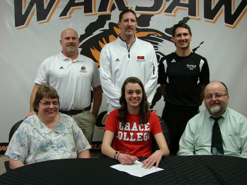 WCHS senior Aletheia Burritt will compete in cross country and track at Grace College. Burritt is shown above with her parents Tami and Mark. In back are WCHS Athletic Director Dave Anson, Grace College cross country and track  coach Jeff Raymond and WCHS girls cross country and track coach Scott Erba (Photo provided)