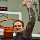 NorthWood boys basketball head coach Aaron Wolfe holds the net after the Panthers beat West Noble 75-61 Saturday night.