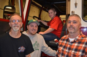 From left are Mentone Firefighters Tim Croy, Brandon Cody and Matt Cohagan. In the driver's seat of the fire truck is Branden Dugan. Dugan will get to attend Hoosier Burn Camp this summer thanks to the men of the Mentone Fire Department and the Kosciusko County Fire Association. (Photo by Stacey Page)