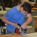 Brendon Schied, a student at Wawasee High School, uses a saw to cut exterior siding for a concessions stand being built by Geometry in Construction students.