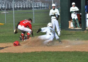 Rylan Kuhn (25) slides in safely at home plate in the third inning of Wawasee's win over Plymouth.
